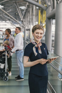 Portrait of smiling airline employee holding tablet at the airport - MFF04722