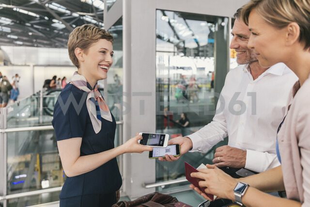 Airline employee scanning QR codes of passengers with smartphone at the airport - MFF04731