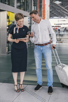 Airline employee with tablet and passenger with cell phone at the airport - MFF04737