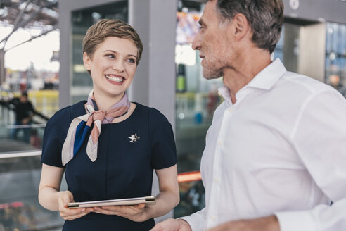 Happy airline employee with tablet talking to passenger at the airport - MFF04740