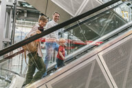 Family with small child going up escalator at CGN airport, Cologne, NRW, Germany - MFF04746