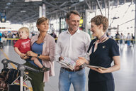 Happy family showing passports to airline employee at the airport - MFF04749