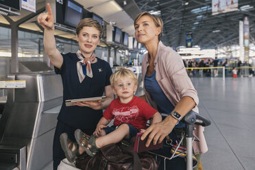 Airline employee assisting mother and child with baggage cart at the airport - MFF04752
