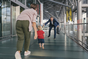 Happy child running into arms of travelling businessman at the airport - MFF04755