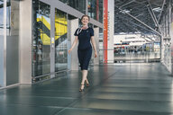 Happy crew member walking in CGN airport, Cologne, NRW, Germany - MFF04761