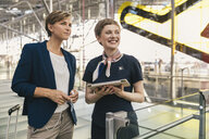 Smiling airline employee with tablet and businesswoman at the airport - MFF04767