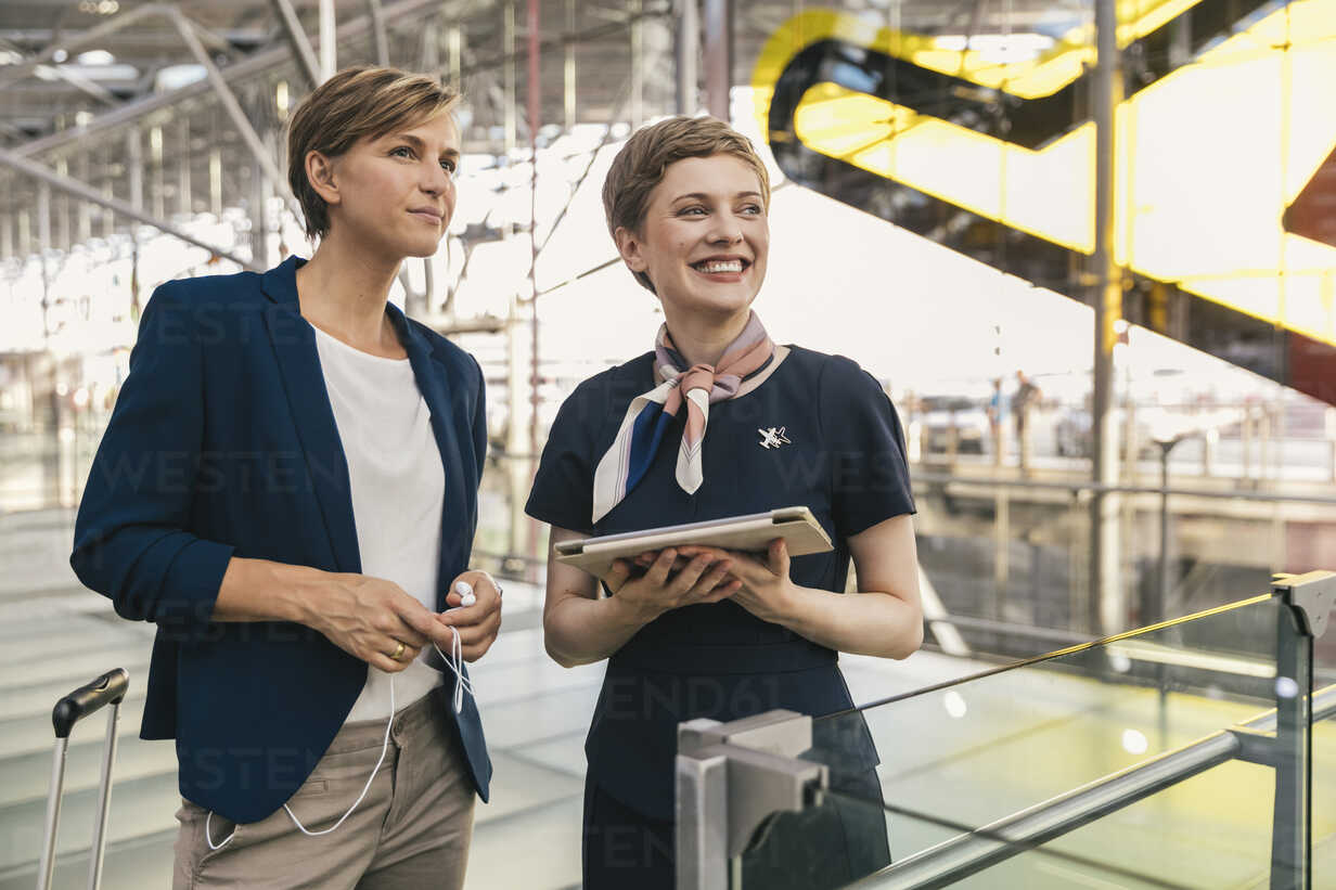 Smiling airline employee with tablet and businesswoman at the airport - MFF04767 - Mareen Fischinger/Westend61