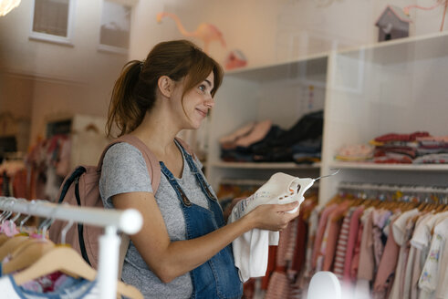 Smiling pregnant woman shopping for baby clothing in a boutique - KNSF05418