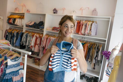 Smiling pregnant woman shopping for baby clothing in a boutique - KNSF05421