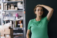 Pregnant woman standing a wall in office looking up - KNSF05430