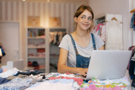 Smiling pregnant woman with laptop in a boutique for baby clothing - KNSF05433