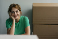 Portrait of smiling woman next to cardboard boxes in office - KNSF05436