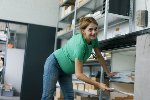 Portrait of smiling pregnant woman working in office - KNSF05445