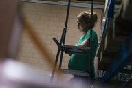 Pregnant woman with ladder in cellar using cell phone - KNSF05451
