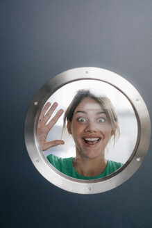 Portrait of woman pulling funny faces behind porthole - KNSF05457