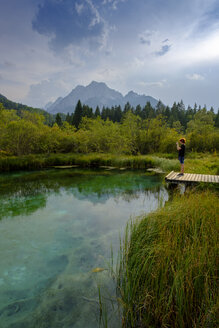 Slovenia, Gorenjska, near Ratece, Sava Dolinka, source, Lake Zelenci, young man standing on jetty - LBF02307