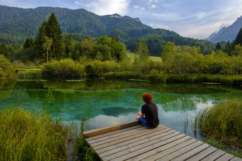 Slovenia, Gorenjska, near Ratece, Sava Dolinka, source, Lake Zelenci, young man sitting on jetty - LBF02310