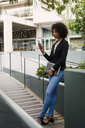 Smiling businesswoman looking at cell phone outdoors - MAUF01998