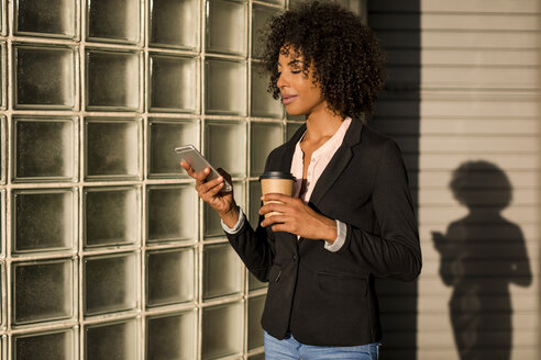 Businesswoman with coffee to go looking at cell phone at evening twilight - MAUF02001