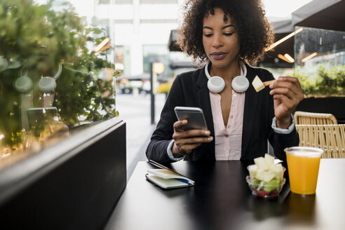 Portrait of businesswoman looking at cell phone at pavement cafe while eating fruit salad - MAUF02019