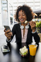 Portrait of smiling businesswoman looking at cell phone at pavement cafe while eating fruit salad - MAUF02022