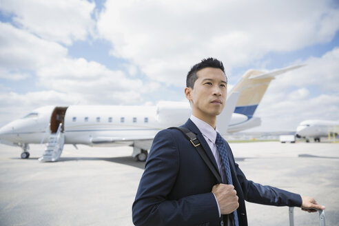 Businessman on tarmac with corporate jet - HEROF01943
