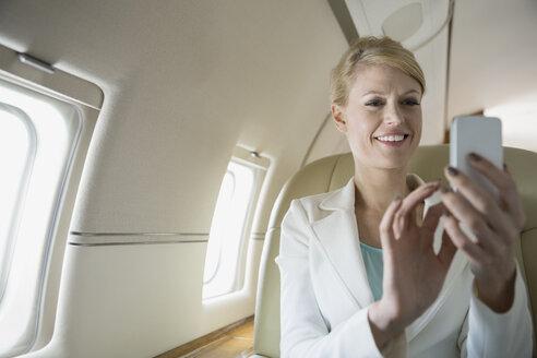 Businesswoman text messaging on corporate jet - HEROF01970