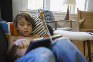 Boy using digital tablet on living room sofa - HEROF01994