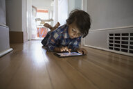 Boy using digital tablet on hallway floor - HEROF01997