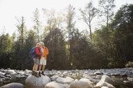 Couple on rock over creek in sunny woods - HEROF02018