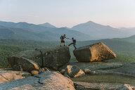 Man helping woman across boulder, PitchoffMountain, Adirondack Mountains, New York State, USA - AURF07949
