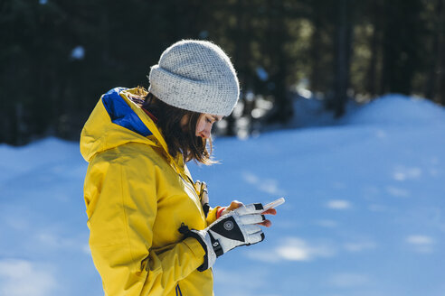 Woman using phone outdoors in winter, Whistler, British Columbia, Canada - AURF08075