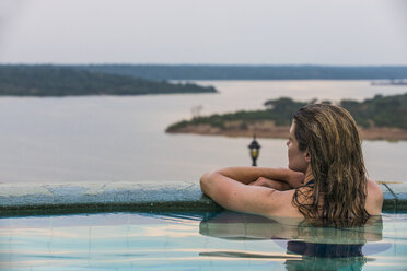 Africa, Uganda, Queen Elizabeth National Park, Woman relaxing in a pool above Kazinga channel - RUNF00509