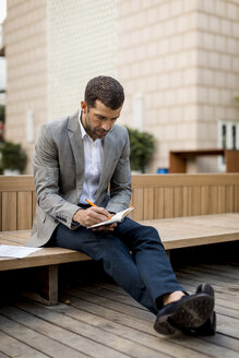 Businessman sitting on a bench writing into diary - MAUF02024