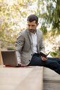 Businessman sitting on a bench using laptop and diary - MAUF02027
