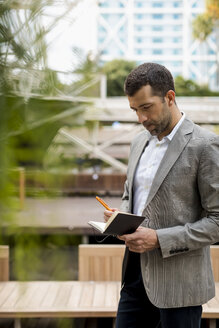 Businessman standing outdoors writing into notebook - MAUF02030