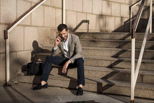 Smiling businessman with bag sitting on stairs talking on cell phone - MAUF02036
