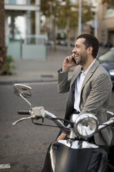 Happy businessman on motorscooter talking on cell phone - MAUF02042