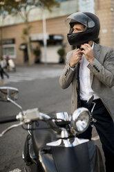 Businessman next to motorscooter putting on helmet - MAUF02045