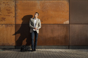 Businessman standing at a wall holding a notebook - MAUF02054