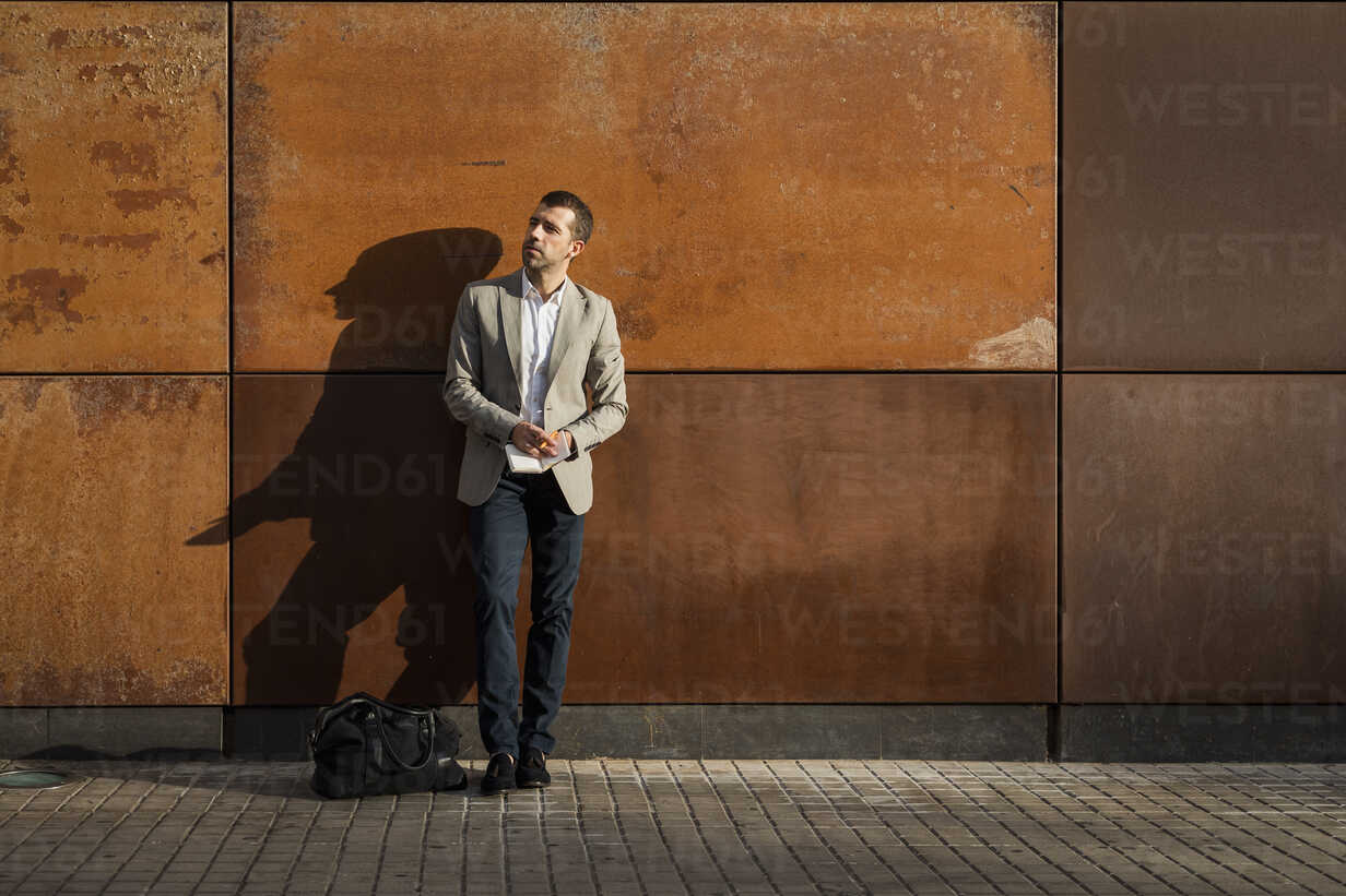Businessman standing at a wall holding a notebook - MAUF02054 - Mauro Grigollo/Westend61