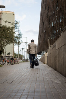 Businessman with bag walking in the city - MAUF02057