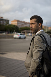 Businessman with bag standing in the city looking around - MAUF02063