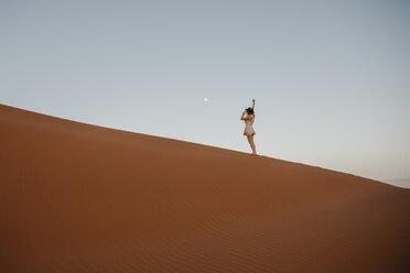 Namibia, Namib desert, Namib-Naukluft National Park, Sossusvlei, woman standing on Elim Dune at sunset - LHPF00233