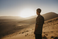 Namibia, Namib desert, Namib-Naukluft National Park, Sossusvlei, man standing at Dune 45 at sunrise - LHPF00242