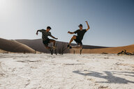 Namibia, Namib desert, Namib-Naukluft National Park, Sossusvlei, two men jumping in Deadvlei - LHPF00248