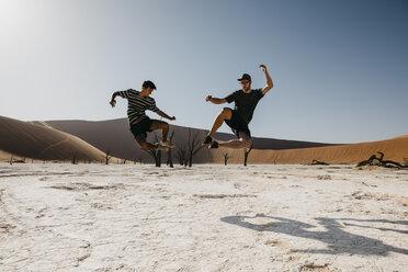 Namibia, Namib desert, Namib-Naukluft National Park, Sossusvlei, two men jumping in Deadvlei - LHPF00248