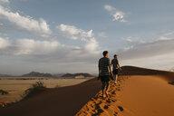 Namibia, Namib desert, Namib-Naukluft National Park, Sossusvlei, two men walking on Elim Dune at sunset - LHPF00254