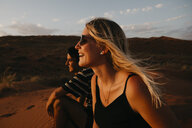 Namibia, Namib desert, Namib-Naukluft National Park, Sossusvlei, happy couple sitting on Elim Dune at sunset - LHPF00257