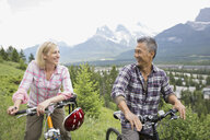 Couple standing with mountain bikes on hillside - HEROF02059